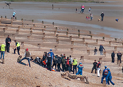 © Licensed to London News Pictures. 16/05/2020. Hastings, UK. A drone watches from overhead (top left) as migrants are helped ashore at Pett Level near Hastings in East Sussex by the emergency services after crossing the English Channel earlier today in an inflatable boat. The group, possibly numbering up to 20 people including young children, were taken under tow by the Hastings Lifeboat and brought ashore by the Pett Level Independent Rescue Boat. They were met by coastguard and other government officials. Photo credit: Andrew Heather/LNP