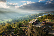Shafts of light beam into the Derwent Valley and illuminate the distant haze. In the foreground, Tumbling Hill, with its gritstone edge and blossoming heather, provides the elevated viewpoint. A summer's evening in the Derbyshire Peak District, England, UK.
