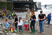 Families looking for artifacts on the river shoreline at low tide on Tower Beach. This part of the Thames beach is only open once or twice a year. Totally Thames takes place over the whole month in September, combining arts, cultural and river events presented by Thames Festival Trust throughout the 42-mile stretch of the River Thames in London, UK.