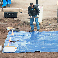 Gallup Police detective Victor Rodriguez lays his findings out on a tarp in the parking lot of the McKinley County Courthouse in Gallup Friday afternoon after construction crews uncover bones Friday morning.