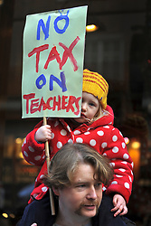 © Licensed to London News Pictures. 30/11/2011, London, UK. 18 month old Hope (surname not supplied) sits on top of her fathers shoulders holding a banner reading No Tax on Teachers. Up to two million public sector workers are staging a strike over pensions in what is set to be the biggest walkout for a generation. Photo credit : Stephen Simpson/LNP