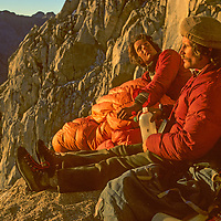 Galen Rowell and Chris Vandiver watch the sunrise at a bivouac site during the first free ascent of Keeler Needle in California's Sierra Nevada.