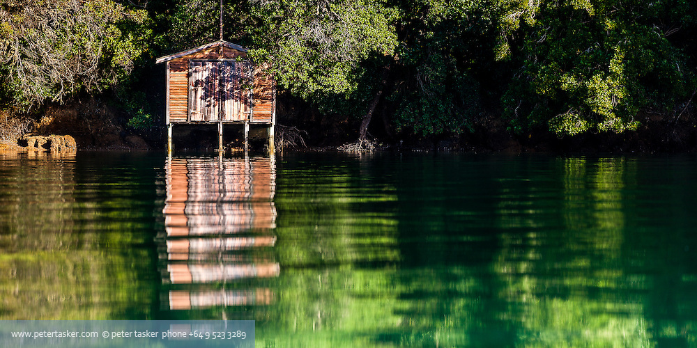 Boat shed surrounded by trees and bathed in morning sunshine. Vivid green yellow and orange reflections on rippled water.
