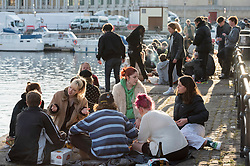 © Licensed to London News Pictures;12/04/2021; Bristol, UK. People sit on the quayside in the evening sunshine at Bristol Harbourside as lockdown restrictions are eased to allow outside hospitality for bars, pubs and restaurants and non-essential shopping on Monday 12 April during the Covid-19 coronavirus pandemic in England. Photo credit: Simon Chapman/LNP.