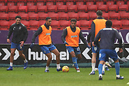AFC Wimbledon defender Terell Thomas (6), AFC Wimbledon striker James Hanson (18), AFC Wimbledon striker Andy Barcham (17) and AFC Wimbledon defender Will Nightingale (5) warming up during the EFL Sky Bet League 1 match between Charlton Athletic and AFC Wimbledon at The Valley, London, England on 15 December 2018.
