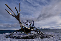 """Sun Voyager (Sólfar). Winter in Reykjavik. From wikipedia """"Sun Voyager is a dreamboat, an ode to the sun. Intrinsically, it contains within itself the promise of undiscovered territory, a dream of hope, progress and freedom."""" Last summer when I visited Reykjavik there were many people surrounding the sculpture, and many more taking pictures. This morning it was snowing and cloudy. The sun started to come out and I found myself alone at the site. Within 5 minutes many more came. Image taken with a Fuji X-T1 mirrorless camera and 12 mm f/2.8 Zeiss lens (ISO 200, 12 mm, f/2.8, 1/3500 sec)."""