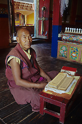 Asia, India, Ladakh, Thikse, Buddhist lama (monk) with prayer book at Thikse gompa (monastery).  PR, MR