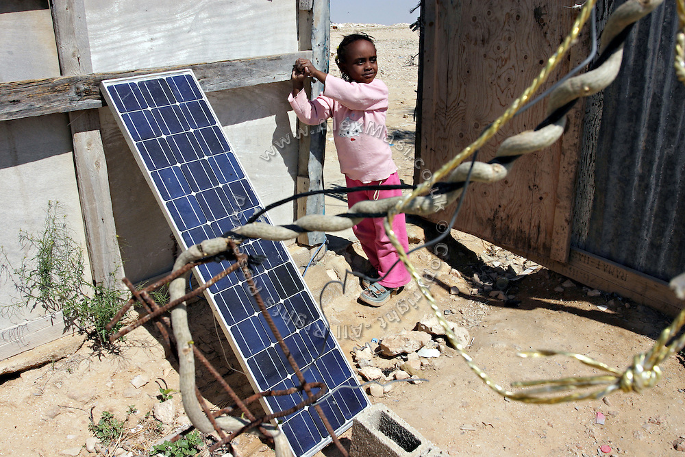 Randa, a 5-year-old girl is standing by a solar panel in the unrecognised village of Wadi el Na'am, pop. 4000, close to Beer Sheva, the capital of the Negev, a large deserted area in the south of Israel.  Wadi el Na'am is located near a large industrial site, Ramat Hovav, and has no infrastructure or electric energy. Water is provided only via storage tanks. It has no health services as the only clinic is deemed illegal and bound to be demolished, as the rest of the structures in the area. Numbering around 200.000 in Israel, the Bedouins constitute the native ethnic group of these areas, they farm, grow wheat, olives and live in complete self sufficiency. Many of them were in these lands long before the Israeli State was created and their traditional lifestyle is now threatened by subtle Governmental policies. The seven Bedouin towns already built are all between the 10 more impoverished towns in Israel. ..