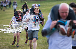 © Licensed to London News Pictures. 06/03/2016. Dorking, UK. Water being thrown over competitors as they take part in the 2016 Wife Carrying Race in Dorking, Surrey.  The race, which is run over a course of 380m, with both men and women carry a 'wife' over obstacles,  is believed to have originated in the UK over twelve centuries ago when Viking raiders rampaged into the northeast coast of  England carrying off any unwilling local women .  Photo credit: Ben Cawthra/LNP