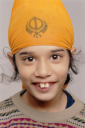 Portrait of young boy wearing turban smiling,