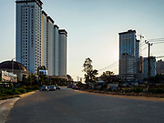 """13 FEBRUARY 2019 - SIHANOUKVILLE, CAMBODIA:  The Xihu Resort Hotel (left) and other casinos under construction in Sihanoukville. There are about 80 Chinese casinos and resort hotels open in Sihanoukville and dozens more under construction. The casinos are changing the city, once a sleepy port on Southeast Asia's """"backpacker trail"""" into a booming city. The change is coming with a cost though. Many Cambodian residents of Sihanoukville  have lost their homes to make way for the casinos and the jobs are going to Chinese workers, brought in to build casinos and work in the casinos.      PHOTO BY JACK KURTZ"""