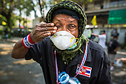 26 DECEMBER 2013 - BANGKOK, THAILAND: An anti-government protestor wipes tear gas out of his eyes during the riot at the Thai Japan Stadium in Bangkok. Thousands of anti-government protestors flooded into the area around the Thai Japan Stadium to try to prevent the drawing of ballot list numbers by the Election Commission, which determines the order in which candidates appear on the ballot of the Feb. 2 election. They were unable to break into the stadium and ballot list draw went as scheduled. The protestors then started throwing rocks and small explosives at police who responded with tear gas and rubber bullets. At least 20 people were hospitalized in the melee and one policeman was reportedly shot by anti-government protestors.      PHOTO BY JACK KURTZ