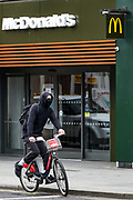 A cyclist is seen wearing face protective mask while waiting for the green traffic light in front of a Closed McDonald Branch near Tottenham Court Road underground station in central London on Monday, May 11, 2020. <br />