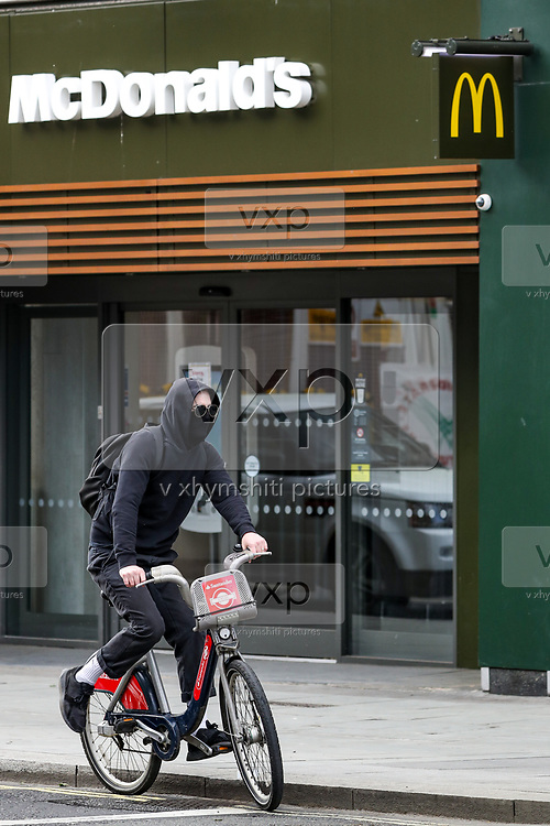 A cyclist is seen wearing face protective mask while waiting for the green traffic light in front of a Closed McDonald Branch near Tottenham Court Road underground station in central London on Monday, May 11, 2020. <br /> U.K. Prime Minister Boris Johnson fleshed out his plan for lifting the U.K. lockdown in Parliament as he seeks to get more people back to work, even as resistance from politicians and labour unions laid bare the hurdles facing the government as it seeks to kickstart the economy. (Photo/ Vudi Xhymshiti)