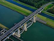 Nederland, Zuid-Holland, Rotterdam, 14-09-2019; Haven van Rotterdam, Botlek, Hartelkanaal met Hartelkering (stormvloedkering) tijdens de jaarlijkse Functioneringssluiting. <br /> De kering, onderdeel van de Deltawerken, vormt samen met de Maeslantkering de Europoortkering en beschermt Rotterdam en achterland bij extreme waterstanden. De keringen worden een maal per jaar, voordat het stormseizoen begint, getest. Tijdens het sluiten van de kering ligt alle scheepvaartverkeer naar de Rotterdamse haven stil. <br /> Aerial view of one of the two storm surge barriers. This barrier, the Hartelkering in the Hartel canal, together with the greater nearby Maeslant barrier (in the New Waterway), are tested during the so-called functioning closure, taking place one a year before the storm season begins. The waterway and canal, leading to the Port of Rotterdam, are closed during the test.<br /> <br /> luchtfoto (toeslag op standard tarieven);<br /> aerial photo (additional fee required);<br /> copyright foto/photo Siebe Swart