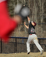 Chester, New York  - An infielder reaches to catch a pop fly as the baserunner heads to first base during the TRUMP March Madness youth baseball tournament at The Rock Sports Park on March 17, 2012.