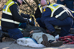 © Licensed to London News Pictures . 11/03/2014 . Barton Moss , Salford , UK . Police Protester Removal Team cuts a protester away from a metal pipe on the road . Anti-fracking protesters on Barton Moss Road at the Barton Moss protest camp today (11th March 2014) as they have lost a court bid against land owners Peel Holdings to remain on their site . Photo credit : Joel Goodman/LNP