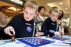 """Cadburys Spots vs Stripes Challenge Race Season Meadowhall Sheffield.Luke and Matthew Chadwick compete for the """"Fastest Coin Stacker"""".2 April 2011.Images © Paul David Drabble"""