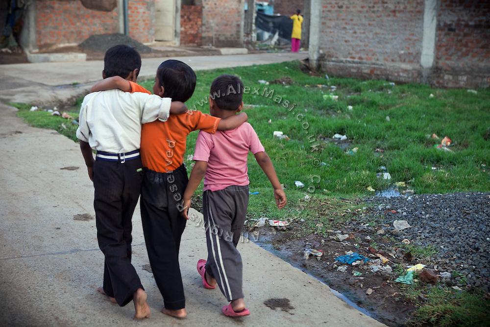 Three children are walking on a road inside one of the water-affected colonies in Bhopal, Madhya Pradesh, India, near the abandoned Union Carbide (now DOW Chemical) industrial complex.