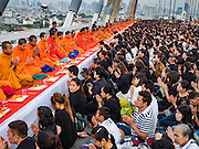 05 DECEMBER 2016 - BANGKOK, THAILAND: People present alms to Buddhist monks during a merit making ceremony on Bhumibol Bridge. Tens of thousands of Thais gathered on Bhumibol Bridge in Bangkok Monday to mourn the death of Bhumibol Adulyadej, the Late King of Thailand. The King died on Oct 13 after a lengthy hospitalization. December 5 is his birthday and a national holiday in Thailand. The bridge is named after the late King, who authorized its construction. 999 Buddhist monks participated in a special merit making ceremony on the bridge.       PHOTO BY JACK KURTZ