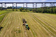Cornwall, New York - A farmer driving a tractor bales hay in a field by the Moodna Viaduct railroad trestle on Aug. 27, 2016.