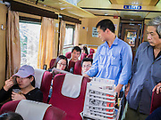 06 APRIL 2012 - HAI PHONG, VIETNAM: A vendor sells newspapers on the Hanoi to Hai Phong Express Train. The Hanoi to Hai Phong Express Train runs several times a day between Long Bien Station in Hanoi and the Hai Phong Station. Hanoi is the capital of Vietnam and Hai Phong is the 4th largest city in Vietnam. Hai Phong is the principal industrial port in the northern part of Vietnam. It was heavily bombed and mined during the American War (what Americans call the Vietnam War).   PHOTO BY JACK KURTZ