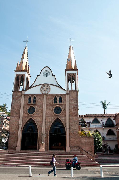 A woman walks under a church in Puerto Vallarta, Mexico. Photo by William Drumm.