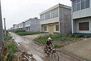 An elderly man bikes passed rolls of newly built houses, mostly shuttered and empty as their younger owners work in the cities,  at a rural village near Fuyang, Anhui Province,  China on 28 August  2013.  As able-bodied adults seek work in cities in hopes of better income, more and more villages in China are inhabited mostly by the elderly and children.