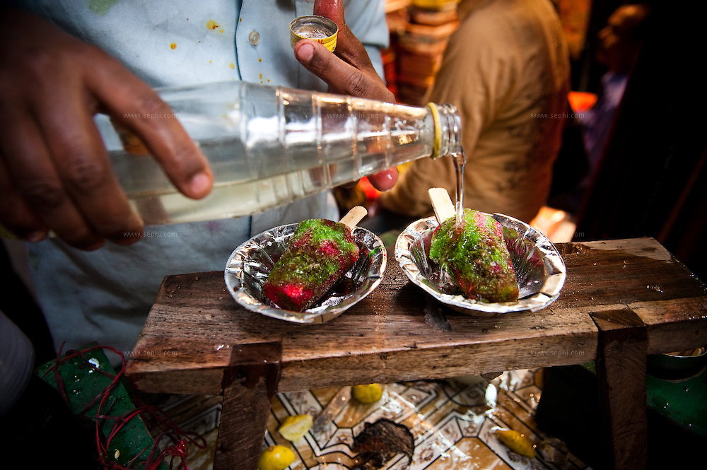 A chuski seller drips colored sugar water and syrup on the crushed ice in the alleies of Old Delhi. Chuski is basically ice on a stick.