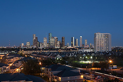 Evening skyline view of Houston, Texas from the west with residential neighborhood in foreground.
