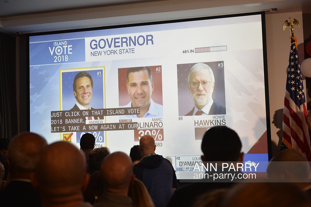 """Garden City, New York, USA. November 6, 2018. With 48% of votes in, Governor Andrew Cuomo is projected as winning re-election, over Marc Molinaro and Howie Hawkins. News 12 Long Island """"Island Vote 2018"""" - projected on large screen - shows how candidates are doing in votes counted so far, as Nassau County Democrats watch Election Day results at Garden City Hotel, Long Island."""