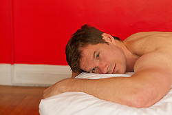 Man in deep thought while resting on a bed