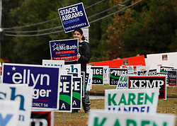 Alyssa Kesselman, from Johns Creek, waves campaign signs outside a Roswell polling place. A steady steam of people vote at the St Mary's Orthodox Church in Roswell. Photo by Bob Andres/Atlanta Journal-Constitution/TNS/ABACAPRESS.COM