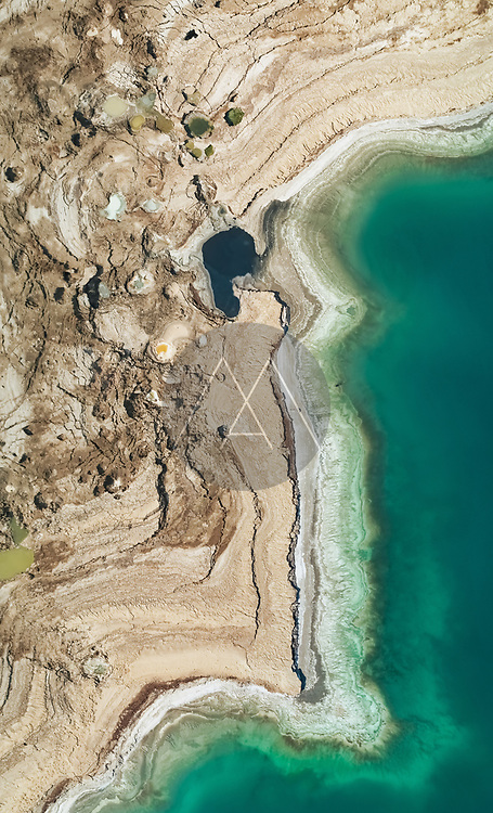 Aerial view of colourful sinkholes along Dead Sea shoreline in Negev, Israel.