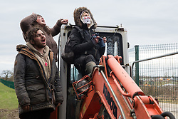 Steeple Claydon, UK. 23 February, 2021. Anti-HS2 activists on a digger sing as they observe an operation by National Eviction Team bailiffs acting for HS2 Ltd to evict them from ancient woodland known as Poors Piece. The activists created the Poors Piece Conservation Project there in spring 2020 after having been invited to stay on the land by its owner, farmer Clive Higgins. Already, local village communities have been hugely impacted by HS2, with 550 acres of land seized including a large section of a nature reserve.