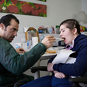 Santa Lucia Foundation, Rome, February 21, 2016. Chiara Insidioso Monda 21-year-old  and her father Maurizio, 44. 21-year-old Chiara has been hospitalized at the Santa Lucia Foundation in Rome since December 2014. In February 2014, when Chiara was only 19, she was brutally beaten by her 'partner', 16 years older than her, till she fell into a coma due to the violence of the blows. The kicks, punches and having her head slammed against a wall caused irreversible damage to Chiara's body and reduced her cerebral functioning to 10%. Chiara had to undergo three brain surgeries when she arrived at the hospital. She woke up from the coma after 10 months and is now in a state of semi-consciousness. This means that she can't talk, move or walk and has to be assisted in every single activity of daily life.<br /><br />Fondazione Santa Lucia, Roma, 21 Febbraio 2016. Maurizio Insidioso Monda, 44 anni con la figlia Chiara, 21 anni. Il padre e la madre di Chiara, Danielle di origini olandesi, sono separati da molti anni la seguono ogni giorno alternandosi in ospedale. La madre passa con lei le mattine, mentre il padre la raggiunge ogni giorno dopo il suo turno di lavoro alle Poste di Fiumicino.