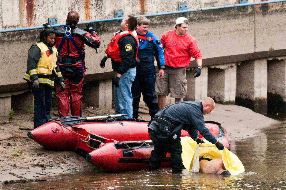 Matt Dixon   The Flint Journal..Rescue workers cover a man's body they removed from the Flint River Sunday afternoon. Witnesses said the man was drunk, took off his shoes, shirt and hat, climbed over the railing near the children's playground and jumped or fell in.
