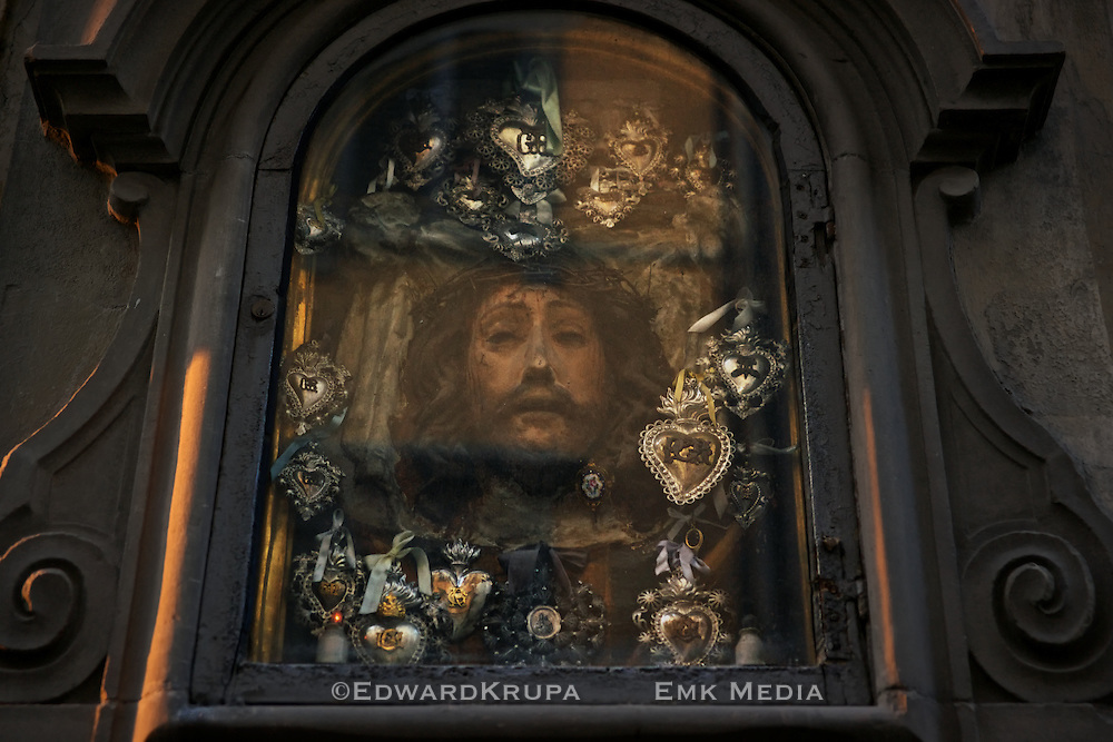A shrine to Jesus Chirst with metal Sacred Hearts inset into a building in Florence, Italy.