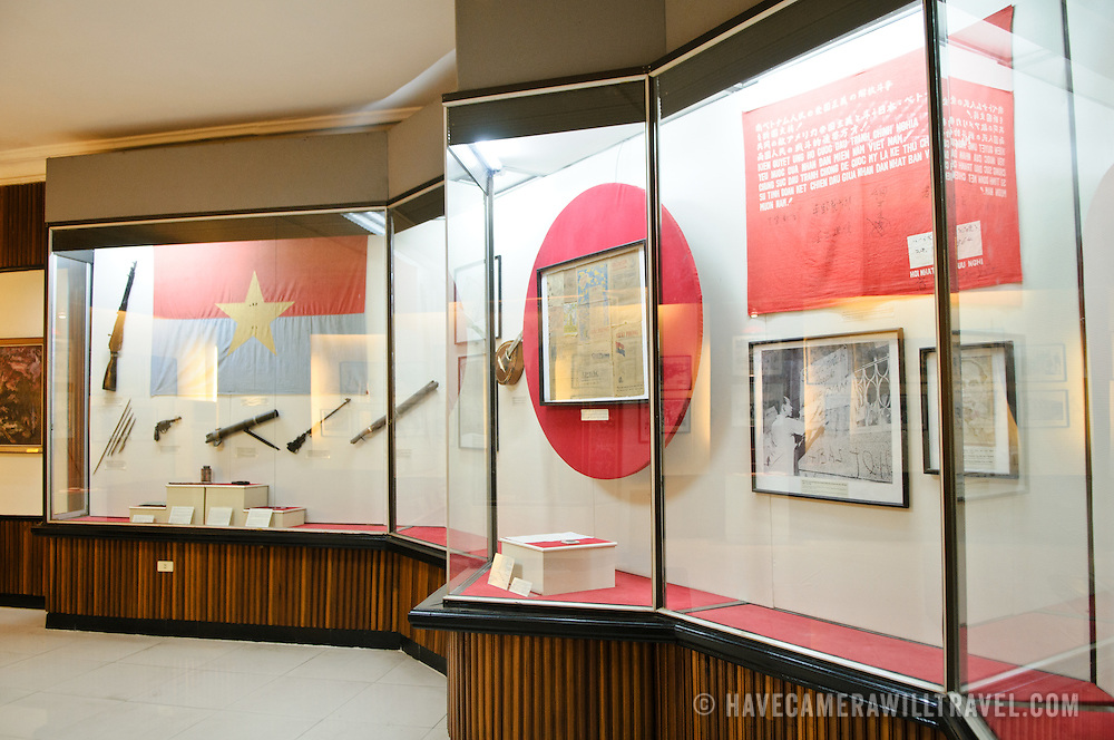 Exhibit cases. At left are revolutionary flags and weapons used in the military campaigns. The Museum of the Vietnamese Revolution in the Tong Dan area of Hanoi, not far from Hoan Kiem Lake, was established in 1959 and is devoted to the history of the socialist revolutionary movement in Vietnam.