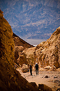 Hikers at the badlands at Golden Canyon in Death Valley National Park, Nevada, USA.