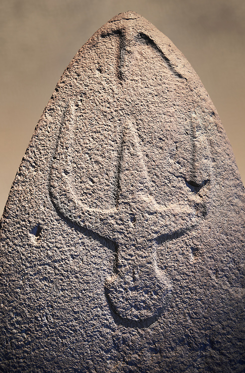 Late European Neolithic prehistoric Menhir standing stone with carvings on its face side. The representation of a stylalised male figure starts at the top with a long nose from which 2 eyebrows arch around the top of the stone. below this is a carving of a falling figure with head at the bottom and 2 curved arms encircling a body above. Excavated from Genna Arrele II. Menhir Museum, Museo della Statuaria Prehistorica in Sardegna, Museum of Prehoistoric Sardinian Statues, Palazzo Aymerich, Laconi, Sardinia, Italy. Warm art background.<br /> <br /> Visit our PREHISTORIC PLACES PHOTO COLLECTIONS for more  photos to download or buy as prints https://funkystock.photoshelter.com/gallery-collection/Prehistoric-Neolithic-Sites-Art-Artefacts-Pictures-Photos/C0000tfxw63zrUT4