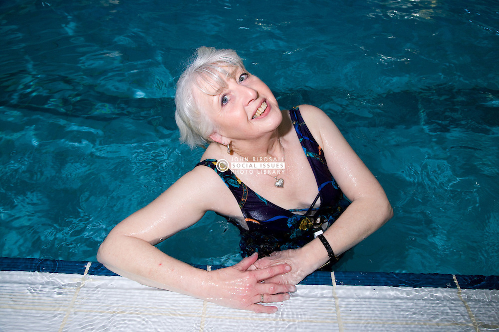 Older woman in the swimming pool at her local leisure centre,