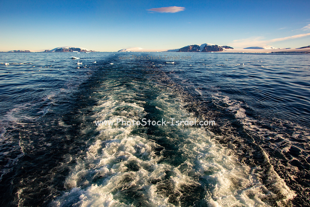 The wake of a zodiac boat departing from an ice mass in the Antarctic South Atlantic