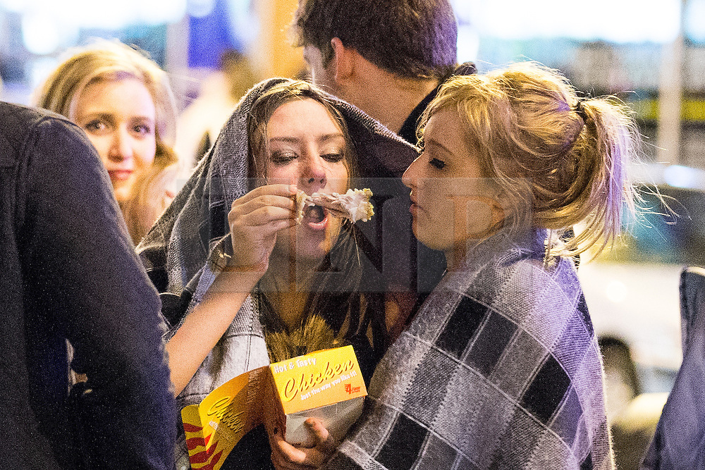 © Licensed to London News Pictures . 01/01/2015 . Manchester , UK . Two women share a chicken takeaway outside the Printworks on Withy Grove . Revellers usher in the New Year on a night out in Manchester City Centre .  Photo credit : Joel Goodman/LNP