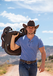 hot rugged cowboy with long brown hair carrying a saddle on a dirt road