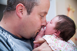 Father kissing newborn baby,