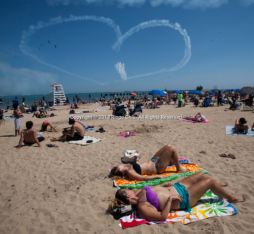 Spectators are watching the U.S. Navy Blue Angeles as they practice for the Air and Water Show on Friday, August 16, 2013 in Chicago, Illinois.  (Photo by Ringo Chiu/PHOTOFORMULA.com)