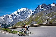 Female yclist rides Scott British mountain bike uphill on The Stelvio Pass, Passo dello Stelvio, Stilfser Joch, in the Alps, Italy