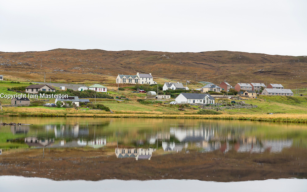 Village of Urafrith reflected in water, Northmavine, Shetland, Scotland, UK