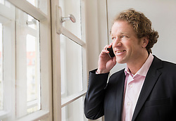 Man in suit on the phone looking out of window